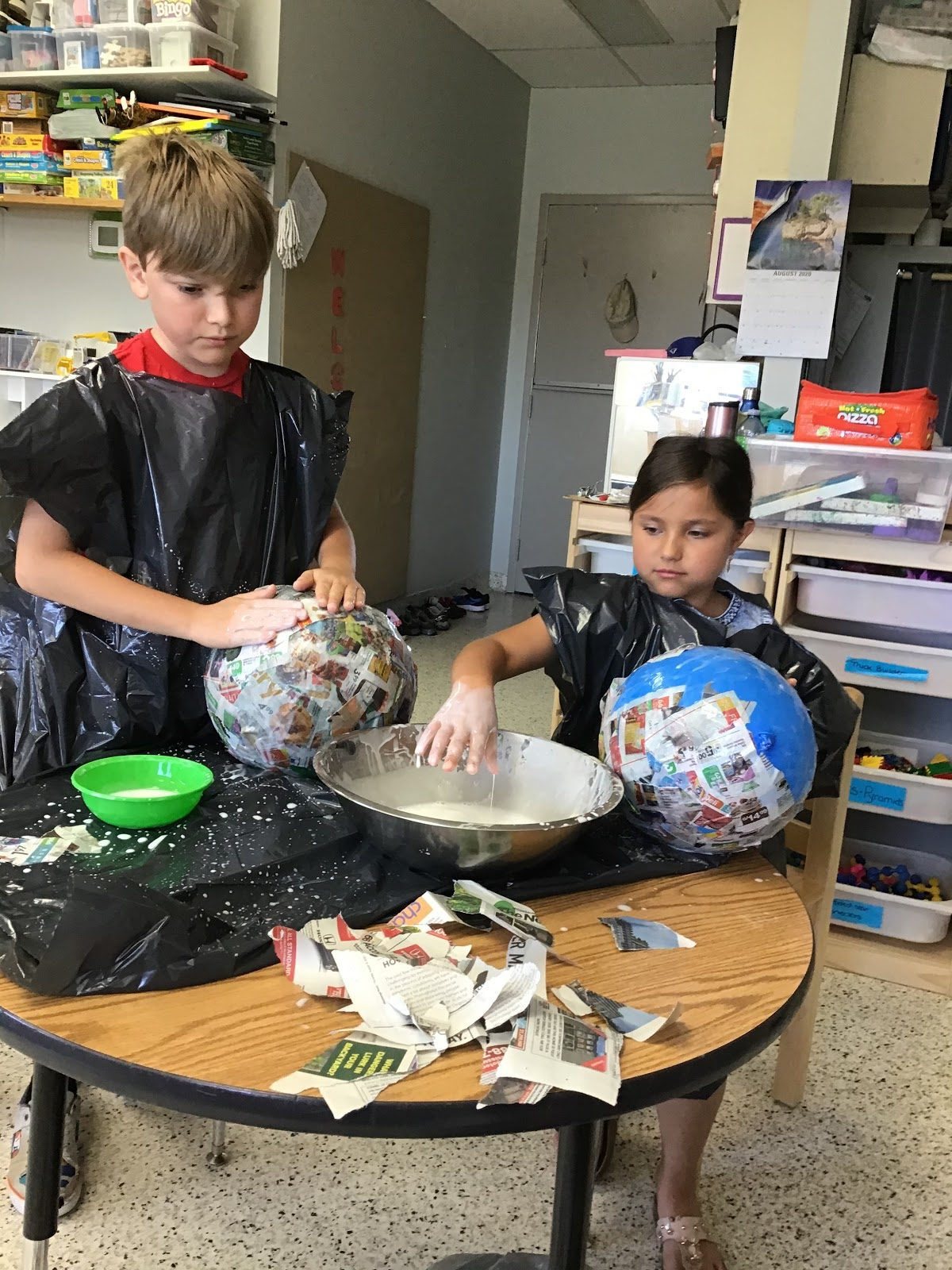 2 kids doing arts and crafts with paper mache