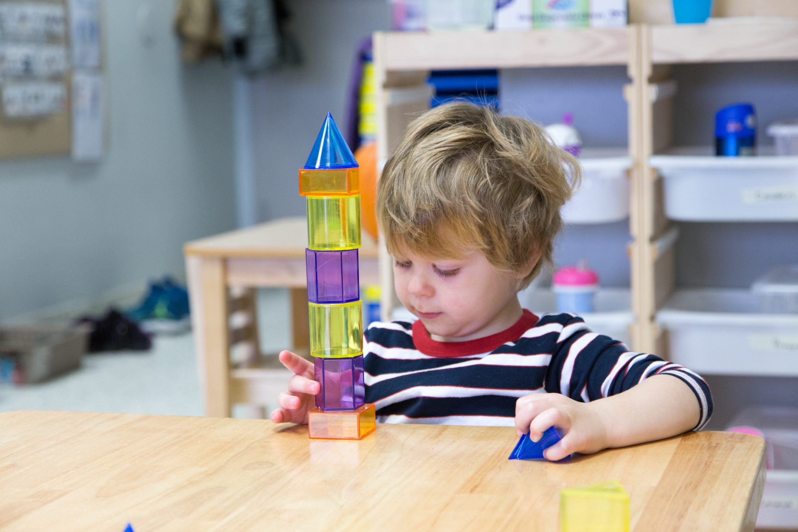 A child playing with plastic geometric block toys